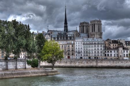 notre dame de paris: Traditional parisian buildings along Seine river and Notre Dame de Paris Cathedral on background in Paris, France.