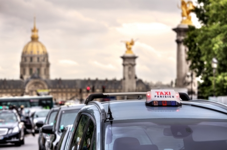 Parisian taxi illuminated sign on the car roof and Les Invalides on the background in Paris, France.