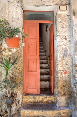 Vertical oriented image of wooden door and old narrow stairs in small house at town of Ventimiglia in Liguria, Italy. photo