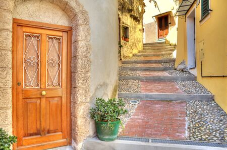 view of a wooden doorway: Wooden door at the entrance to small house on narrow cobbled street in town of Ventimiglia in Liguria, Italy.