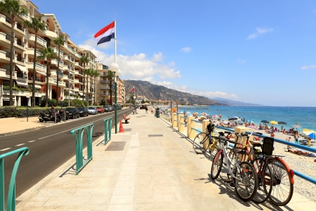 menton: MENTON - JULY 07: Promenade along seashore and hotels in Menton (aka The Pearl of France) - the town on French Riviera and famous touristic resort in Menton, France on July 07, 2012. Editorial
