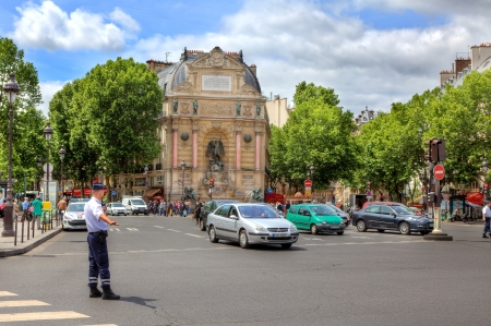 PARIS - JUNE 06: Policeman regulates traffic at Place Saint-Michel public square in front of monumental fountain constructed in 1858-1860 during French Second Empire by the architect Gabriel Davioud in Paris, France on June 06, 2012.