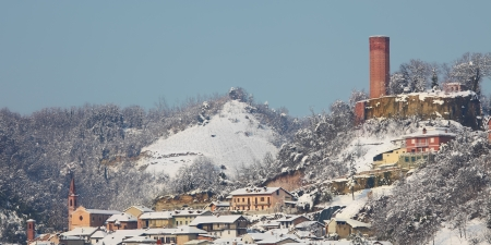 Panoramic view on small town, churches and ancient castle tower among snowy hills in Piedmont, Northern Italy  photo