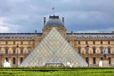 PARIS - JUNE 06: Facade of Pyramid and Louvre Museum (former Royal Palace) on background. Louvre is one of the main touristic sites ans Pyramid serves also as entrance to the museum on June 06, 2012 in Paris, France.