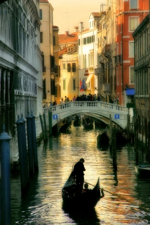 Vertical oriented image of gondola passing on small canal among historic houses in Venice, Italy
