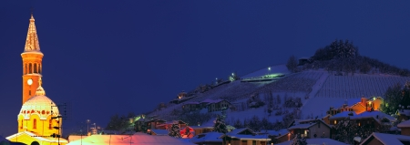 Panoramic view on church and snowy hill with houses at night in Alba, Italy. photo