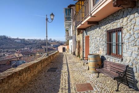 empedrado: Calle pavimentada de piedra estrecha y casas antiguas de la ciudad de La Morra, el norte de Italia