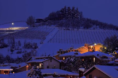 View on snowy hill with houses at evening in town of Alba in Piedmont, Northern Italy  photo