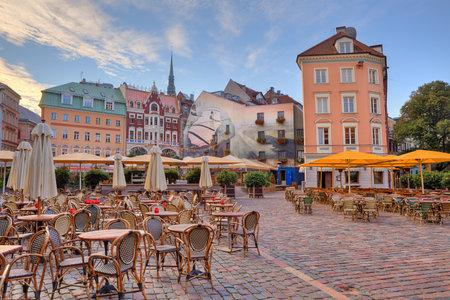 Ciudad empedrada plaza con restaurantes al aire libre entre los edificios de colores en Riga, Letonia