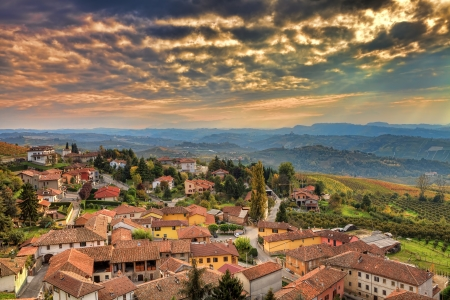 Aerial view on small italian town among hills under beautiful cloudy autumnal sky at sunset in Piedmont, Northern Italy.