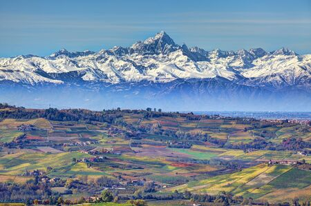 Aerial view on hills and meadows of Piedmont and snowy mountain peaks on background at autumn in Northern Italy.