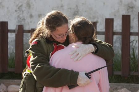 army girl: ASHKELON - JANUARY 10: An israeli soldier from the rescue team holds and hugs young girl who was witness of missile launched by Hamas terrorists from Gaza explode near her house on January 10, 2009 in Ahskelon, Israel.