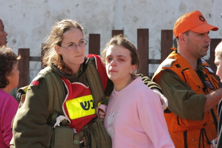 ASHKELON - JANUARY 10: An israeli soldier from the rescue team holds and hugs young girl who was witness of missile launched by Hamas terrorists from Gaza explode near her house on January 10, 2009 in Ahskelon, Israel. Stock Photo - 16506736