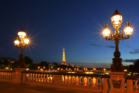 historic site: PARIS - JULY 10: Famous Eiffel Tower with night illumination and beautiful lampposts on Alexander the Third (Alexander III) bridge on July 10, 2007 in Paris, France