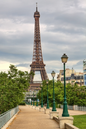 Vertical oriented image of famous Eiffel Tower and traditional urban lampposts in Paris, France.
