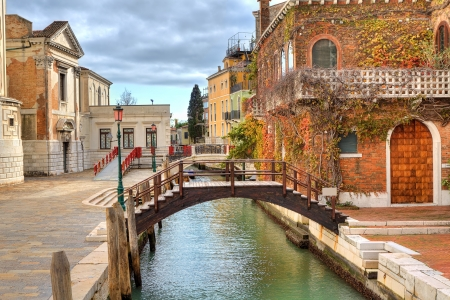 Small wooden bridge over narrow canal and traditional venetian brick house covered with ivy in Venice, Italy.