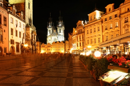 Old Town Square aka Stare Mesto with people  motion blured , opened restaurants, illuminated buildings and Tyn Church on background at evening in Prague, Czech Republic  Reklamní fotografie