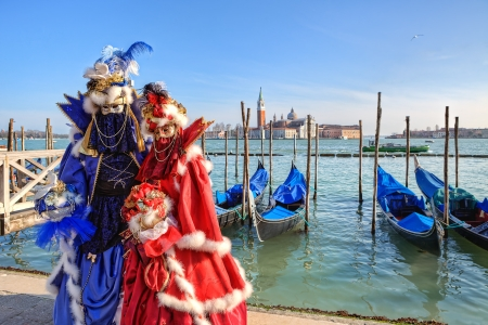 VENICE - MARCH 04: Two participants wear red and blue dresses, costumes and masks standing near gondolas on Grand Canal and San Giorgio Maggiore church on background during famous traditional venetian carnival taking place every year in Venice, Italy on M