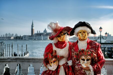 venice mask: VENICE - MARCH 04: Two participants wear red costumes and golden masks standing on small bridge as Grand Canal and San Giorgio Maggiore church on background during famous traditional venetian carnival taking place every year in Venice, Italy on March 04,  Editorial