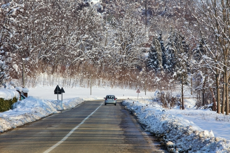 Car on the road among trees on fields covered by snow at winter in Piedmont, Northern Italy  photo