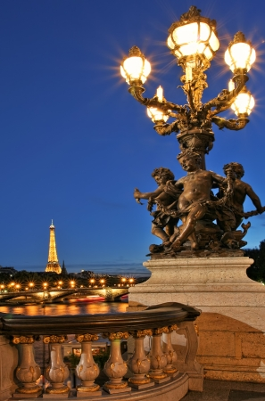 PARIS - JULY 10: Vertical oriented image of famous Eiffel Tower with night illumination and beautiful lamppost on Alexander the Third (Alexander III) bridge. The Eiffel Tower and the bridge are most visited monuments in Paris, France on July 10, 2007.