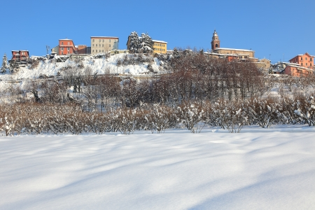 Rural field covered by white snow and small town with colorful houses on the hill on background under blue winter sky in Piedmont, Northern Italy. Stock Photo - 17480725