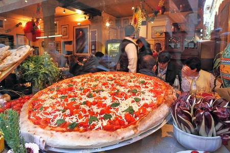 VENICE - MARCH 04: Big round plate of pizza with red tomatoes and cheese displayed on restaurant window and visitors inside on background. Pizza is traditional italian dish very popular around the world in Venice, Italy on March 04, 2012.