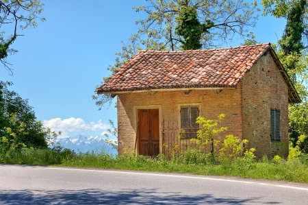 Small rural brick house near road among trees in Piedmont, Northern Italy  photo