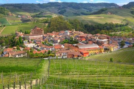 イタリア北部の春の緑の丘とピエモンテのブドウ畑の間でバローロの町に表示します。