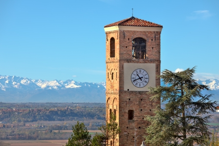 View on old brick belfry tower with big clock and mountains with snowy peaks on background under blue sky in Piedmont, Northern Italy  photo