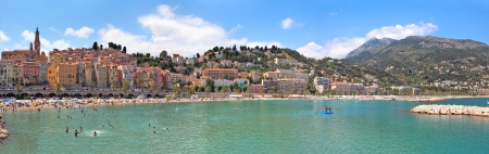 MENTON - JULY 07: Panorama of small medieval town of Menton with red houses along public beach on hot summer day. The town is very popular holiday resort on French Riviera in Menton, France on July 07, 2012. Stock Photo - 18113006