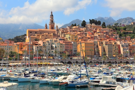 french riviera: View on colorful houses, church and marina with yachts and boats in Menton - town on French Riviera in France  Stock Photo