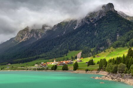 Small village on sunny valley among alpine lake with calm turquoise color water and mountain peaks under cloudy sky in Switzerland  photo