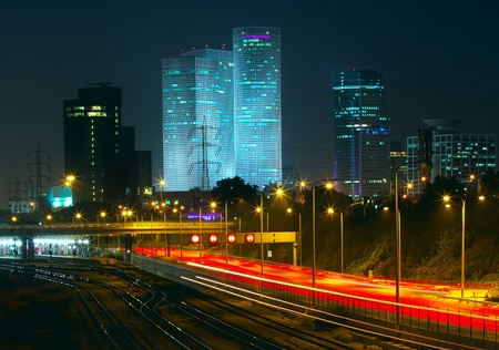 azrieli center: Night view of Tel Aviv city downtown, illuminated Azrieli towers and light traces on Ayalon highway