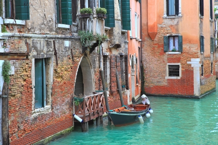 Small boat tied next to old red brick house with wooden balcony on narrow canal in Venice, Italy  photo