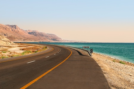 serpentine: Highway runs along Dead Sea and red mountains in the desert in Israel