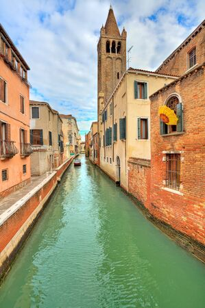Vertical oriented image of narrow canal among old typical houses and belfry tower on background in Venice, Italy  photo