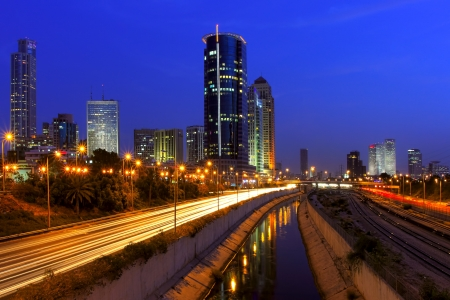 azrieli: Evening view on illuminated modern office buildings, Azrieli towers  and light traces on Ayalon highway in downtown of Tel Aviv, Israel