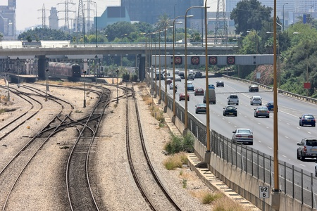 Railway lines and station with train along Ayalon highway with flowing traffic in city center at rushhour in Tel Aviv, Israel  photo