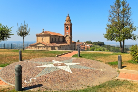 View on red brick church under blue sky from small park in town of Diano D Stock Photo - 18393518