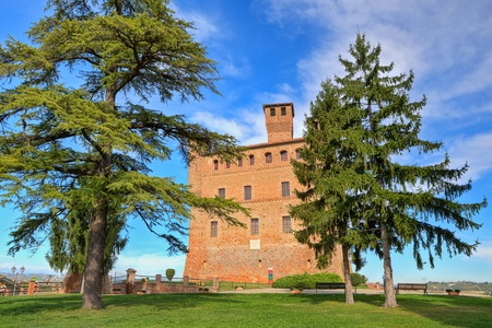 cavour: View on red brick ancient castle among trees under blue sky with white clouds in Grinzane cavour, Piedmont, Italy