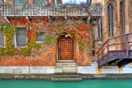 Vine covers facade of red brick house next to narrow canal and small wooden bridge in Venice, Italy  photo