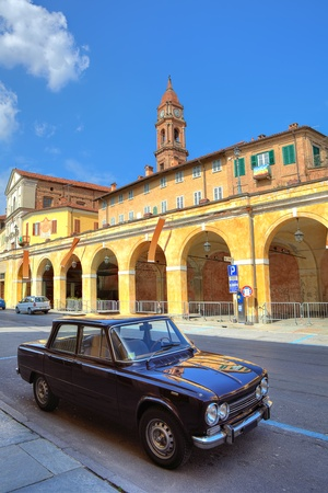 Vertical image of old black car from 60s stands on the street in front of yellow arched passage and red brick belfry under blue sky at town of Bra in Piedmont, Northern Italy  Stock Photo - 18646308