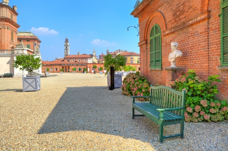 racconigi: Wooden bench on the gravel pathway next to red brick house at the entrance to park and Royal Castle of Racconigi in Piedmont, Northern Italy  Editorial