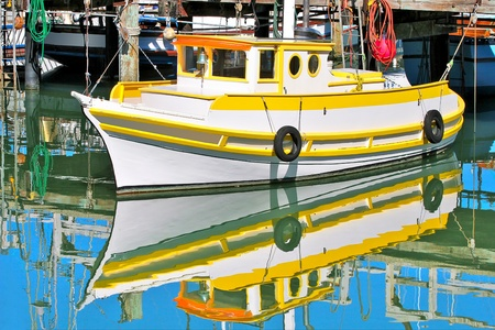 Yellow and white fishing boat moored at dock  and reflected with blue sky in the calm water of San Francisco marina in California, USA  photo