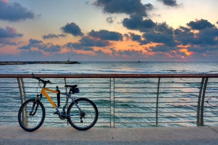 Mountain bike stand on promenade on the background of Mediterranean sea and beautiful sunset sky with clouds in Tel Aviv, Israel  photo