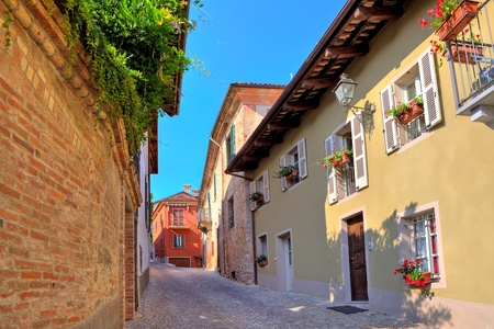 Narrow cobbled street among old brick wall and colorful houses in small town of Guarene in Piedmont, Northern Italy Stock Photo - 19059138