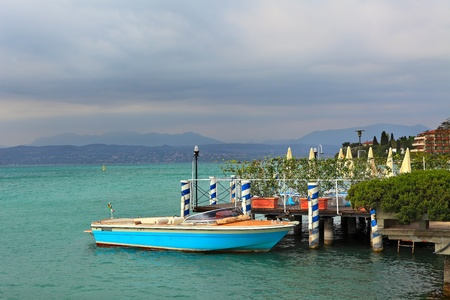 sirmione: Boat moored at the peer under cloudy sky on Lake Garda in Sirmione, Italy