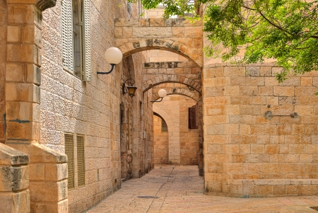 Narrown cobbled street among traditional stoned houses of jewish quarter at old historic part of jerusalem, Israel  스톡 콘텐츠