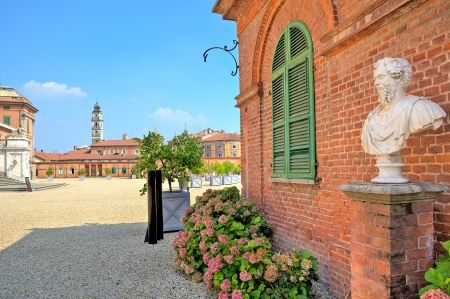 racconigi: Bust on pedestal on the gravel pathway next to red brick house at the entrance to park and Royal Castle of Racconigi in Piedmont, Northern Italy
